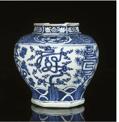 A BLUE AND WHITE HEXAGONAL JAR, JIAJING (1522-1566) painted with bamboo, prunus and pine issuing from rockwork jutting out from rolling waves, their branches growing in the form of auspcious characters, the shoulder decorated with quatrefoil cartouches of crane amongst scrolling clouds alterating with stylised lotus flowers on a inverted y-formed hatch ground, the rim with further floral panels — 9¾in. (24.8cm.) high.