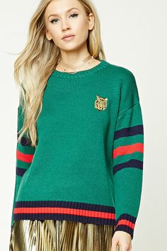 A lightweight ribbed knit sweater featuring an embroidered tiger chest logo, a round neckline, dropped shoulders, long sleeves with a stripe pattern, striped trim, and a boxy silhouette.