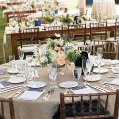 Peach garden roses, blue thistle and dusty miller filled mercury-glass vases on round and farm-style reception tables.