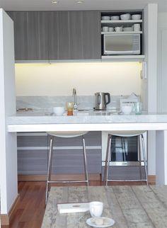 La cocina refuerza la apuesta por la estética moderna, con muebles bajo mesada y alacenas en madera enchapada en melamina gris topo y detalle de perfilería de acero (Estudio Lima).
