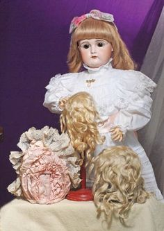 """PRETTY GERMAN BISQUE CHILD DOLL BY KESTNER. Marks: 15. 26"""". Bisque socket head, brown sleep eyes, painted lashes, feathered and brushstroked brows, pierced ears, slightly open mouth, shaded and accented lips, upper teeth, blonde human hair wig, composition ball-jointed body, contemporary white cotton and lace frock, antique black leather shoes; also includes antique white cotton dress and undies. Commentary: Very fine quality bisque and modeling, lovely facial decoration"""