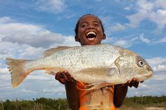 Happy girl holds a big fish on the beach in a small fishing village near Morondava, Madagascar.   And yes, this fish was our delicious dinner :)  Website: Dietmar Temps, photography Blog: Dietmar Temps, travel blog