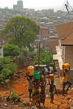 Children carrying water home in the afternoon in the steep hills over Destruction Bay, Freetown, Sierra Leone Guinea Conakry, French West Africa, African Image, Destinations, African Countries, Guinea Bissau, Beautiful Places To Visit, Africa Travel, Continents