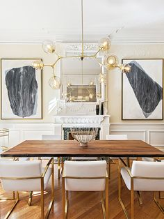 Glam dining room with gold accents, monochrome art, and classic architectural details