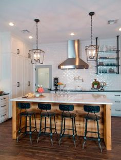The kitchen in the McKenzie home has been completely transformed, a wall was knocked down to open and create more space. Some key elements of the kitchen are the stainless steel appliances, vent hood, custom island, and a subway inspired tile backsplash, as seen on Fixer Upper. (after)