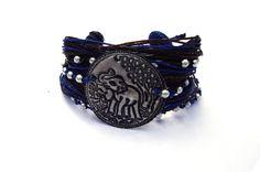 Brede armband gemaakt van verschillende dunne draadjes bruin en blauw waxkoord. Gedecoreerd met kraaltjes met in het midden een dun metalen schildje met een afbeelding van een olifant. Lengte inclusief sluiting 22 cm. Breedte 4 cm. Hele aparte armband! Zie afbeelding.