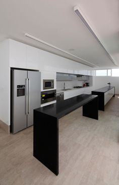 Stunning Desert Home Designed in Cool Contemporary Style: Long Black Island In The Deployed House Kitchen With The White Drawers And Some Wh...