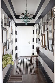 A turquoise chandelier adds a pop of unexpected color to this striped hallway.