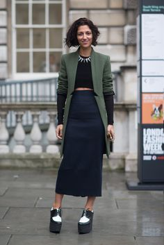 """Just dandy! Yasmin Sewell in cropped long-sleeved black sweater, white statement necklace, long olive blazer with """"cut"""" collar detailing, calf length pencil skirt, black and white platform lace-ups. Very cool!"""
