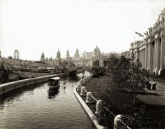View looking west across a lagoon toward the Palace of Machinery and the Ferris Wheel at the 1904 World's Fair. Missouri History Museum