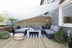 Bois clair, voile claire et mur foncé, voici un exemple d'aménagement de terrasse. http://www.jardinsdexcellence.com/index.php