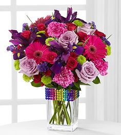 lavender roses, purple iris, hot pink gerbera daisies, hot pink spray roses, fuchsia carnations, green button poms, purple statice, & lush g...
