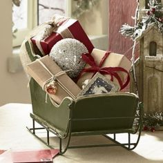 """Tabletop Sleigh Create a festive centerpiece with this Tabletop Sleigh. Just fill it with your favorite ornaments, faux greenery, mini wrapped gifts—whatever your holiday heart desires. Wire runners; metal bracing. Composite wood; rustic, painted finish. 19"""" l x 7 1/4"""" w x 10 1/2"""" h."""