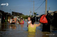 PHILIPPINES, Bulacan : Residents wade through a flooded street in  Calumpit, Bulacan province on October 22, 2015. The death toll from a  ferocious typhoon in the Philippines climbed to 54 on Thursday, as  home-wrecking floods shifted downstream to coastal villages, displacing  tens of thousands of residents. AFP PHOTO / NOEL CELIS
