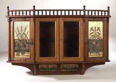 Aesthetic Movement oak wall cabinet, semi bowed form, the spindle galleried surmount above two central glazed doors, flanked by two doors featuring painted and gilt panels with summer flowers, 133cm wide, 89cm high, 26cm deep