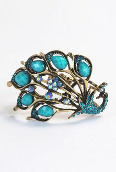 """Peacock hinged bracelet  STYLE # CL0023307  $19.95  Color: Dull gold/turquoise    A dramatically wrought cuff boasts sweeping wings of dull gold tone wrapped around a beautiful peacock setting of sparkling stones.        Hinge with magnetic closure.      Approx. inner circumference: 6 3/4"""".      Approx. setting dimensions: 4""""W x 2 1/2""""L.      Base metal/acrylic/crystals."""