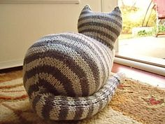 """This is the second in my series of house cats!With paws tucked in and tail to his side, The Parlor Cat makes a very prim and proper house guest. Knit in the round, it is one piece from head to tail, and a befitting 10"""" long and 7"""" wide."""