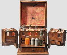German medical supply travel kit 18th cent., Walnut casket with iron fittings,  The front sides open, displaying interior with 5 drawers and 16 compartments with 12 glass medicine bottles & 4 pewter ointment tins. 19 X 18.5 X 18.5 cm.