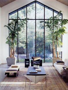 モダンなインテリアと、背の高いダイナミックな観葉植物がホテルのロビーのように洗練されたリビングです。