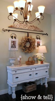 use a decorative curtain rod for hanging pictures or decor