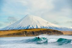 o by Chris Burkard on Aleutian Islands as Alex Gray carves up a beautiful wave catching a glimpse of the active volcano peak. Alex Gray, Giant Waves, Big Waves, Water Surfing, Surfer Magazine, Travel Photographer, Oeuvre D'art, Les Oeuvres, Cool Photos