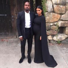 Kim Kardashian West wore a black Valentino cape gown to a weekend wedding with Kanye West.