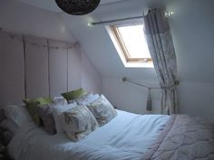 small loft space converted into welcoming bedroom, alternative dressing of a velux skylight window. eyelet curtains in laura ashley avebury amethyst with bacall amethyst band detail. headboard covered in laura ashley bacall amethyst, cushions made to co ordinate