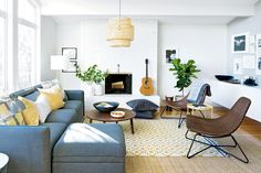 love the bright feel of this room. love the use of mid century modern furniture. i also love how they brought in color through pillows, art, and lamps