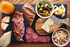 ein halbes Baguette aus Weizenmehl mit Prociutto und Salami, serviert auf einem Teller aus Lavastein, ein kleines Küchenbrett aus Holz mit einer kleinen Messer für Hackfleisch darauf, eine weiße Schüssel mit Oliven und eine weiße Schüssel mit Nüssen, ein Einmachglas mit Honig mit fester Textur