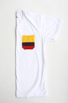 Wayuu Camiseta blanca, bolsillo con los colores de la bandera de Colombia en tejido artesanal.