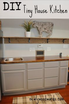 A DIY tiny house kitchen with painted stock cabinets, stained and Waterloxed butcher block countertops, and a barn wood open shelves.