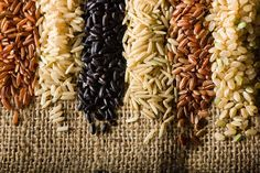 Six Varieties of Raw Brown Rice. From left to right: 1. Himalayan Red Rice - 2. Long-Grain Brown Rice - 3. Chinese Forbidden Black Rice - 4. Brown Basmati Rice - 5. Riz Rouge Camargue or French Red Rice - 6. Short-Grain Brown Rice.