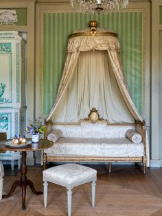 Canopied day bed in cream against a green striped wall