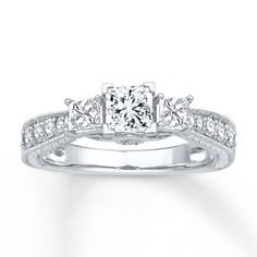 Representing your past, present and future, a trio of gorgeous princess-cut diamonds crowns this three-stone engagement ring for her. Round diamonds and milgrain flow along the band to complete the look. Styled in 14K white gold, the ring has a total diamond weight of 1 carat. Diamond Total Carat Weight may range from .95 - 1.11 carats.