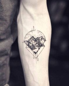 Graphic mountain tattoo on the left inner forearm.