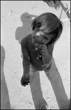 Bruce Davidson 1965 Almeria. Child eating grapes, shadow of Bruce Davidson overlapping. (Spain)