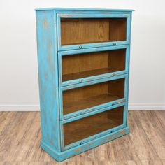 This shabby chic lawyer's bookshelf is featured in a solid wood with a distressed light blue chalk paint finish. This barrister bookcase has 4 shelf cabinets and glass front doors that lift up. Great for displaying books and knick knacks! #shabbychic #storage #bookcase&shelving #sandiegovintage #vintagefurniture