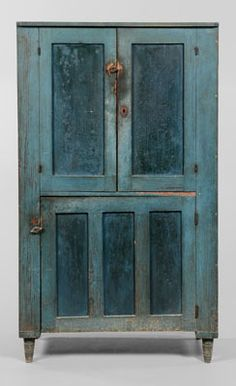 TWO-TONE PAINTED CUPBOARD WITH TWO-PANELED DOORS OVER A SINGLE TRIPLE-PANELED DOOR.