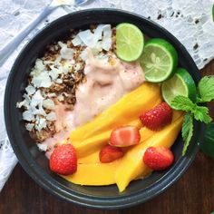 Strawberry Banana Ice-Cream! with mangoes, strawberries, homemade granola, toasted coconut, lime and mint on top. Just Blend 3 frozen bananas with a handful of strawberries