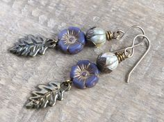 This autumnal pair of earrings feature Greek cast metal oak leaf charms, in a warm antique bronze finish. Above, I have added beautiful Czech glass primrose flower beads in a lovely shade of opaque violet with a vintage style gold wash. The earrings are finished with pale moss green melon shaped beads, which sit snugly inside Vintaj brass foilage bead caps. The earrings have small Vintaj brass French hook earwires and measure approximately 4 1/2 cm (1 3/4 inches) from the bottom of the…