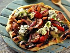 Grilling pizza crust gives it a deliciously crisp exterior. Bobby makes his Grilled Pizza with grilled sausage, peppers and onions and also tops it with a creamy oregano-spiked ricotta.