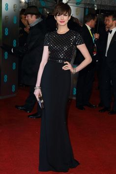 February 10 2013 To the BAFTA Awards Best Supporting Actress winner Anne Hathaway wore a Burberry gown with studded bodice and carried an Anya Hindmarch clutch.