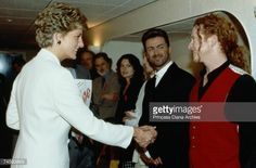 1993--shakes hands with singer Mick Hucknall of Simply Red at a rock concert for World AIDS Day at Wembley, London, 2nd December 1993