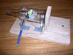 Here is a bottle cutter that I made to cut pop bottles into drinking glasses. I used a couple scrap pieces of plywood, some shower door rollers and a cheap glass cutter from Lowes. To cut a bottle, a. Cutting Glass Bottles, Recycled Glass Bottles, Liquor Bottles, Bottles And Jars, Perfume Bottles, Wine Bottle Art, Diy Bottle, Wine Bottle Crafts, Bottle Cutter