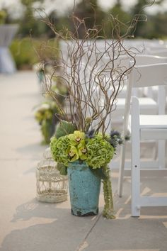 Love the blue patina container with the green hydrangea and orchids with the natural willow...perfect aisle accents for a beach wedding!