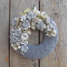 Ehhez az ajtódíszhez egy kis méretű alapot készítettem, amit szürke frotír anyaggal vontam be. A frotír textúrájának és az anyag színének köszönhetően a felület betonszerű hatást kelt. Az így elkészített alap bal felső ívét textil hortenzia virágokkal, hamvasított termésekkel, krém színű pik golyókkal borítottam. A termések közötti réseket szárított tillandsiával és mohával töltöttem ki. Saját készítésű horgolt virágokkal és egy pici üveglencsével fedett stilizált óraszámlappal díszítettem…