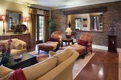 Nice feel. Inviting colors. Tuscan style family room with a warm brick wall and curtains to control light. The large chairs and sofa are perfect for any family to read,...