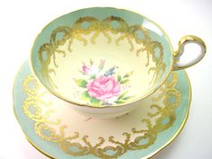 Very nice tea cup and saucer from Aynsley    Nice gold filigree on the green with a pink rose inside the tea cup as well as on the saucer    The