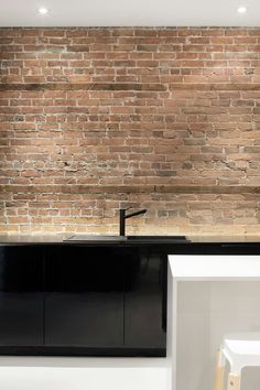 all black kitchen with bricks is epic .. but I really like the recessed lighting under the countertops