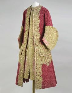 Parade ensemble (kaftan and camisole), made in France, circa 1727-1730.  This ensemble, comprising a coat of coarse cut velvet, and a waistcoat of patterned brocade, represents a part of a court male costume of the early XVIIth century. The other part was the knee-length breeches. The double-breasted knee-length coat, made of red silk velvet, is close-fitting the chest.  The laps, cuffs and side slits are ornamented with floral pattern of gold lace and lower laps are trimmed with silver…